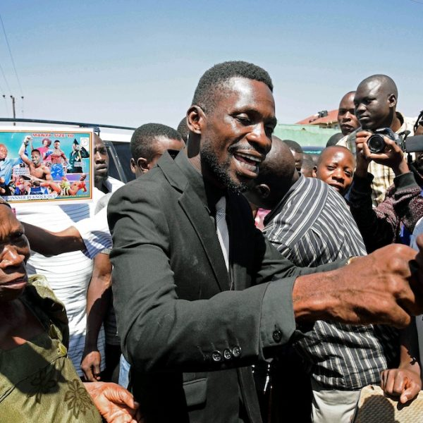 "Musician turned politician, Robert Ssentamu Kyagulanyi commonly known as ""Bobi wine"" (C) greets his supporters in a suburb of Kampala on June 30, 2017.  For the last decade Ugandans have known two presidents: Yoweri Museveni, the country's long-time ruler, and musician Robert Kyagulanyi a.k.a. Bobi Wine, a.k.a. His Excellency the Ghetto President. But in a surprising turn the 35-year-old reggae star -- who was just three when Museveni took power at the head of a rebel army -- on June 29, won a landslide victory in a city by-election to become the country's newest lawmaker.  / AFP PHOTO / ISAAC KASAMANI"